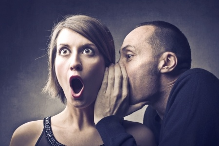 12648731 - man telling a secret to an astonished woman